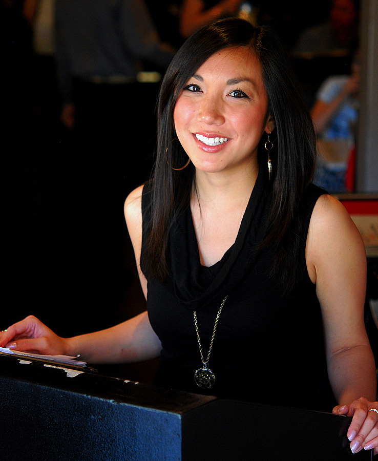 hostess at restaurant in black dress smiling smile