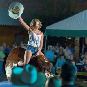 mechanical bull girl waving hat